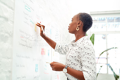 Buy stock photo Shot of a young businesswoman brainstorming with notes on a wall in an office