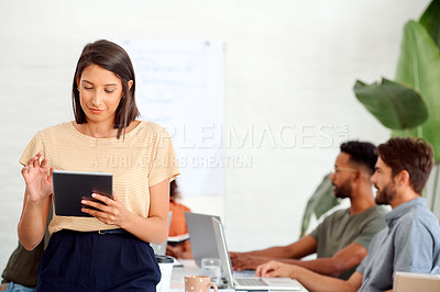 Buy stock photo Shot of a young businesswoman using a digital tablet in an office with her colleagues in the background