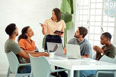 Buy stock photo Shot of a businesswoman using a digital tablet while giving a presentation to her colleagues in an office