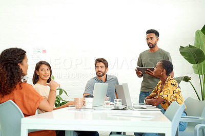 Buy stock photo Shot of a businessman using a digital tablet while giving a presentation to his colleagues in an office