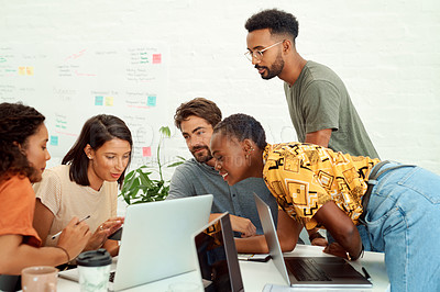 Buy stock photo Shot of a group of businesspeople working together on a laptop and digital tablet in an office