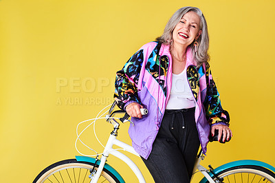 Buy stock photo Portrait of a confident and stylish senior woman posing with her bicycle against a yellow background