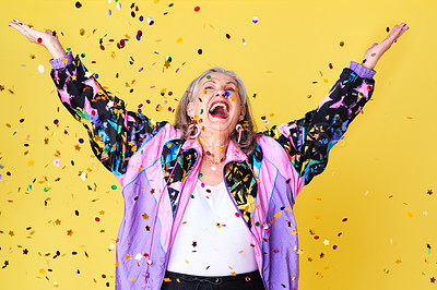 Buy stock photo Cropped shot of a cheerful and stylish senior woman celebrating with confetti falling over her against a yellow background