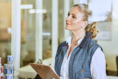 Buy stock photo Cropped shot of an attractive mature supervisor standing with her clipboard during a stocktake in a warehouse