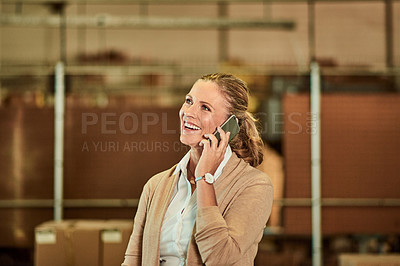 Buy stock photo Cropped shot of an attractive mature supervisor standing alone and talking on her cellphone in a warehouse