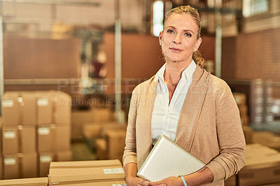 Buy stock photo Cropped portrait of an attractive mature supervisor standing alone and using a tablet during a stocktake in a warehouse
