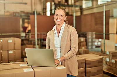 Buy stock photo Cropped portrait of an attractive mature supervisor standing alone and using a laptop during a stocktake in a warehouse
