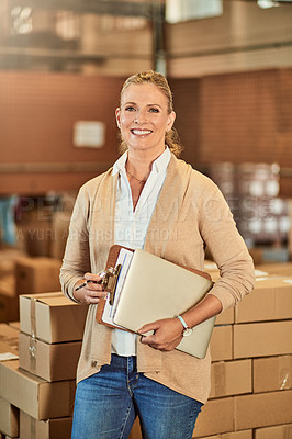 Buy stock photo Cropped portrait of an attractive mature warehouse supervisor standing alone and holding a clipboard and laptop after a successful stocktake
