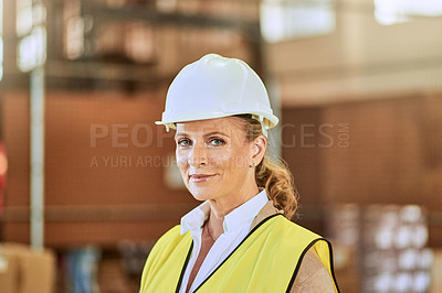 Buy stock photo Cropped portrait of an attractive mature supervisor wearing safety gear and standing alone in a warehouse