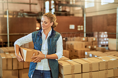 Buy stock photo Cropped shot of an attractive mature supervisor standing alone and holding a box during a stocktake in a warehouse