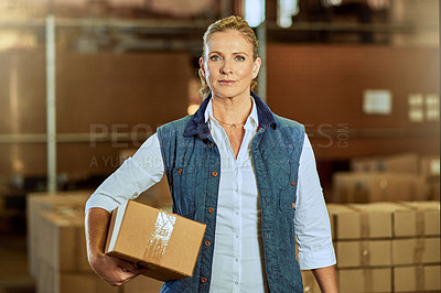 Buy stock photo Cropped portrait of an attractive mature supervisor standing alone and holding a box in a warehouse
