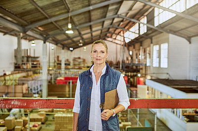 Buy stock photo Cropped portrait of an attractive mature supervisor standing alone and holding a clipboard after a stocktake in a warehouse