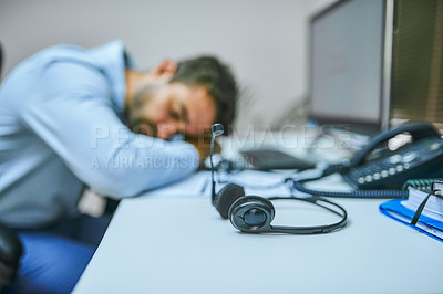 Buy stock photo Shot of a call centre agent sleeping with his head on his desk
