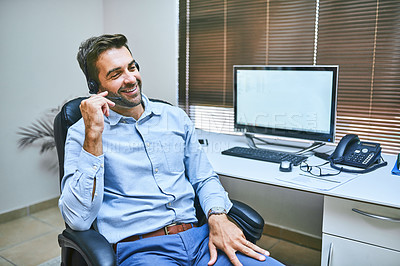 Buy stock photo Shot of a call centre agent wearing his headset while sitting in the office