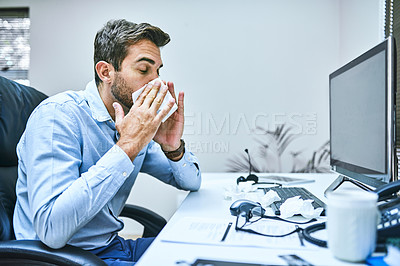 Buy stock photo Cropped shot of a businessman blowing his nose into a tissue while sitting at his desk