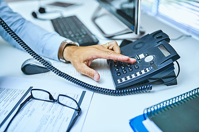 Buy stock photo Cropped shot of an unrecognizable businessman using the telephone at his desk