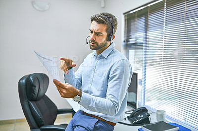 Buy stock photo Shot of a call center agent wearing his headset while in the office