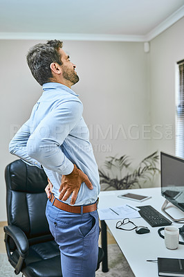 Buy stock photo Shot of a businessman experiencing back pain while standing in his office