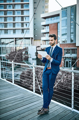 Buy stock photo Shot of a businessman using a digital tablet while standing on a bridge