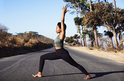 Buy stock photo Full length shot of an attractive young woman practicing yoga while standing on a road outdoors