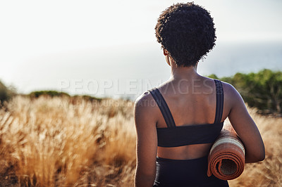Buy stock photo Rearview shot of an unrecognizable woman holding a yoga mat while standing outdoors during the day