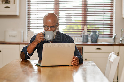 Buy stock photo Cropped shot of a senior man drinking coffee and using a laptop while relaxing at home