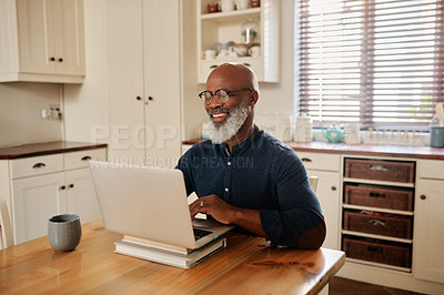 Buy stock photo Cropped shot of a mature man using a laptop while relaxing at home