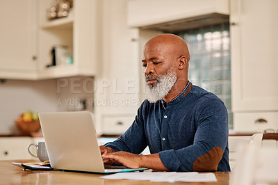 Buy stock photo Cropped shot of a mature man using a laptop while going over his bills and paperwork at home