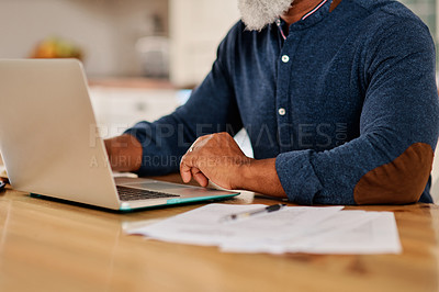 Buy stock photo Cropped shot of an unrecognizable mature man using a laptop while going over his bills and paperwork at home