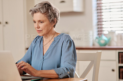 Buy stock photo Cropped shot of a mature woman using a laptop while relaxing at home