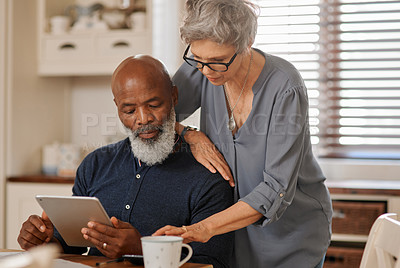 Buy stock photo Cropped shot of an affectionate and happy senior couple using a digital tablet while relaxing together at home