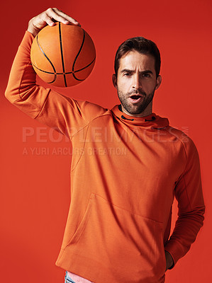 Buy stock photo Studio shot of a handsome young man playing basketball against a red background