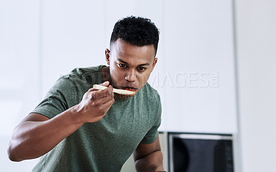 Buy stock photo Cropped shot of a handsome young man tasting the food he's cooking in his kitchen at home