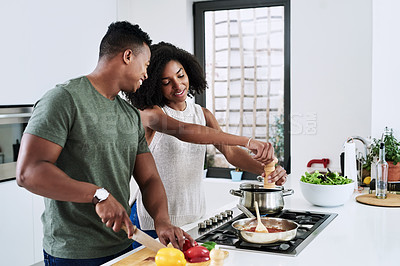Buy stock photo Cropped shot of a happy young couple cooking a meal together inside their kitchen at home