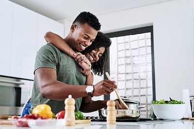 Buy stock photo Cropped shot of an affectionate and happy young couple cooking a meal together inside their kitchen at home