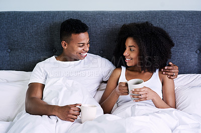 Buy stock photo Cropped shot of a happy young couple having coffee while lying in bed
