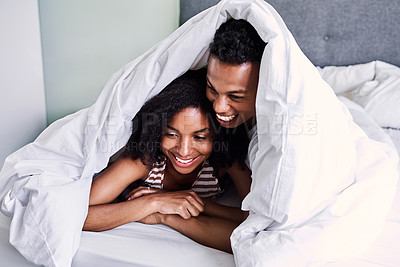 Buy stock photo Cropped shot of happy young couple relaxing and spending time together in their bedroom at home