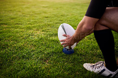 Buy stock photo Cropped shot of an unrecognizable sportsman crouching alone during rugby practice in a sports club