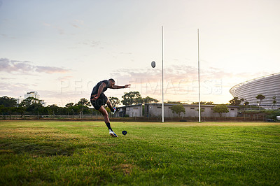 Buy stock photo Full length shot of a handsome young sportsman kicking a rugby ball during an early morning training session