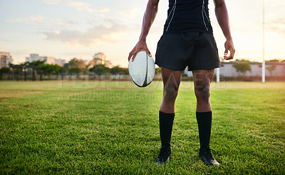 Buy stock photo Cropped shot of an unrecognizable sportsman standing alone and holding a rugby ball during a morning practice