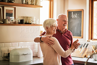 Buy stock photo Cropped shot of an affectionate senior couple dancing with each other in their kitchen during the day