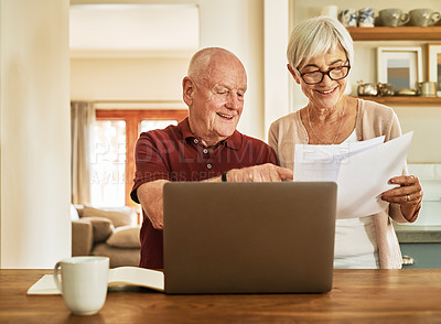 Buy stock photo Cropped shot of a happy senior couple using a laptop to calculate their home finance during a day at home