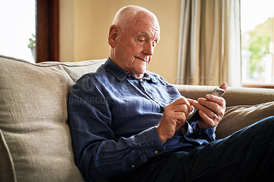 Buy stock photo Cropped shot of a senior man sitting alone on the sofa and using a cellphone during a day at home