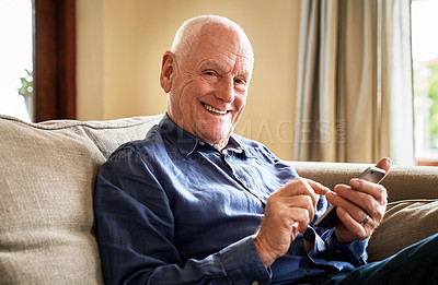 Buy stock photo Cropped portrait of a senior man sitting alone on the sofa and using a cellphone during a day at home