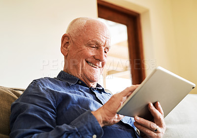 Buy stock photo Cropped portrait of a senior man sitting alone on the sofa and using a tablet during a day at home