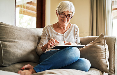 Buy stock photo Cropped shot of an attractive senior woman sitting alone in her living room and using a tablet