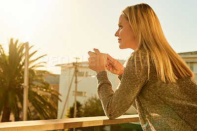 Buy stock photo Shot of an attractive mature woman enjoying a cup of coffee on the balcony of her home