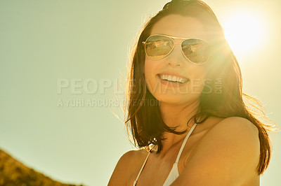 Buy stock photo Cropped shot of a beautiful young woman wearing sunglasses while spending the day in the sun