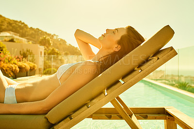 Buy stock photo Shot of a young woman relaxing on a deck chair by the poolside