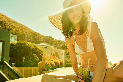 Buy stock photo Shot of a woman wearing her bikini while relaxing with a drink in her hand